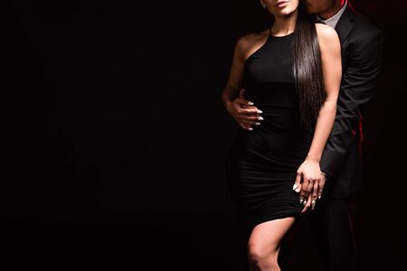 Cropped view of elegant couple embracing on black background