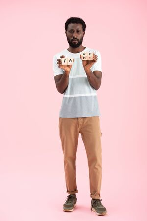 Handsome African American man holding alphabet cubes with fact word, isolated on pink background