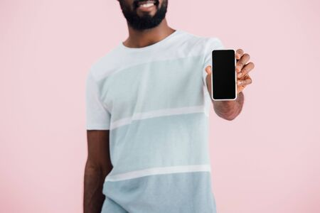 Cropped view of African American man holding smartphone with blank screen, isolated on pink background