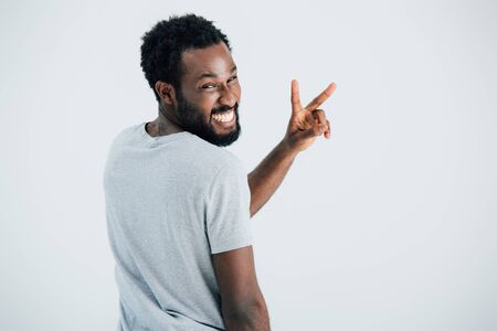 Happy African American man in grey t-shirt showing victory sign isolated on grey background