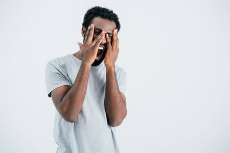 African American man in grey t-shirt screaming and crying isolated on grey background Stock Photo