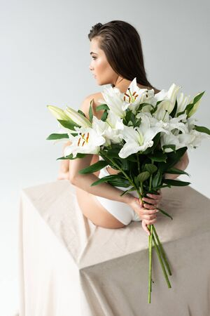 Back view of tender young woman in white lacy bodysuit holding bouquet of lilies isolated on white background Stock Photo