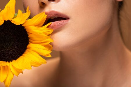 Cropped view of young woman with yellow sunflower and open mouth