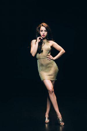 Sexy giovane donna elegante in abito trasparente dorato in posa isolato su sfondo nero