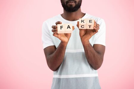Cropped view of African American man holding alphabet cubes with fact word, isolated on pink background