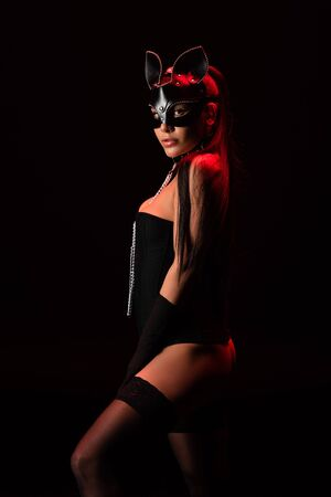 Sexy bdsm girl in corset and mask looking at camera isolated on black background