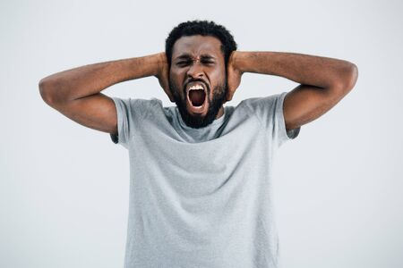 Emotional African American man in grey t-shirt screaming and closing ears isolated on grey background