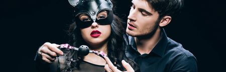 Panoramic shot of handsome young man holding gag near woman in mask and costume isolated on black background