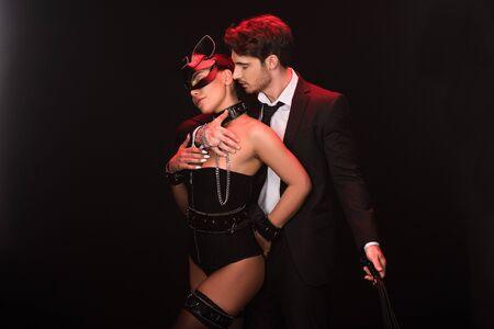Couple sexy avec fouet fouet isolé sur fond noir Banque d'images