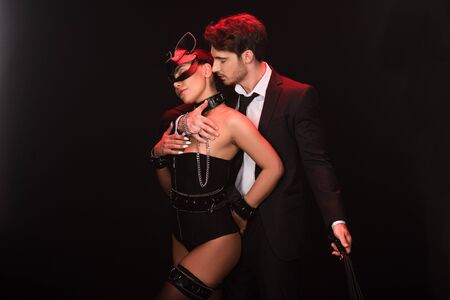Sexy bdsm couple with flogging whip isolated on black background