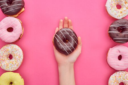 Partial view of woman holding chocolate doughnut on bright pink background