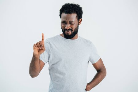 Beard African American man in grey t-shirt pointing up isolated on grey background Stock Photo