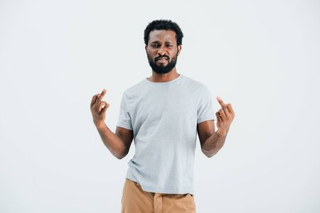 Beard African American man in grey t-shirt showing middle fingers isolated on grey background