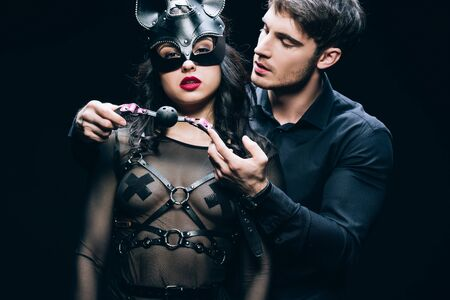 Young man holding gag near sexy woman in mask and bdsm costume isolated on black background Archivio Fotografico