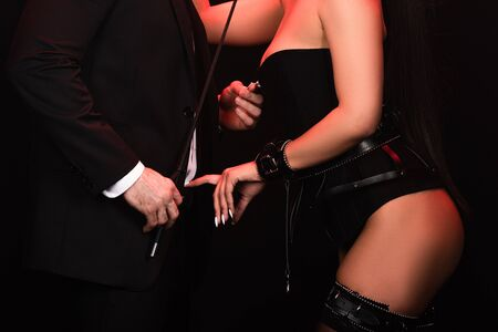 Cropped view of bdsm couple with stack on black background