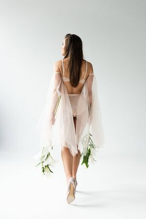Back view of tender young woman walking with lilies isolated on white background