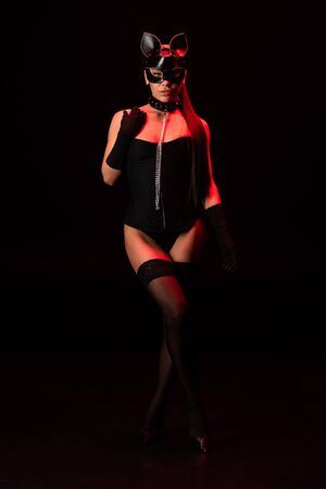 Full length view of sexy bdsm girl in corset and mask on black background Фото со стока - 126296679