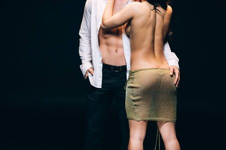 Back view of naked woman with sexy buttocks standing near elegant boyfriend with bare torso isolated on black background
