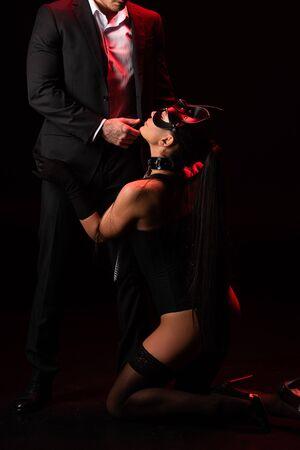 Bdsm girl in mask standing on knees beside man in formal wear on black background