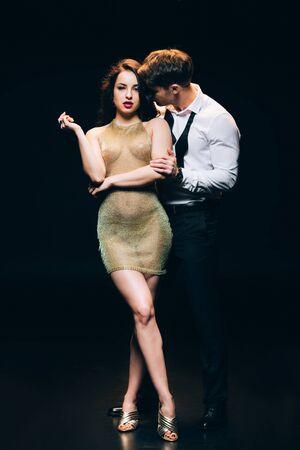 Elegante jonge man zoenen hete jonge meisje in transparante jurk geïsoleerd op zwarte achtergrond