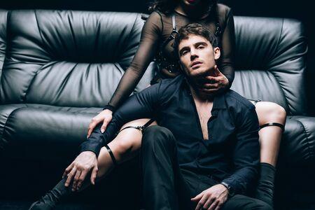 Leidenschaftlicher gutaussehender Mann, der neben einer Frau im Kostüm auf einem schwarzen Ledersofa sitzt