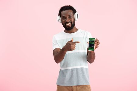 African American man listening music with headphones and pointing at smartphone with booking app, isolated on pink background Standard-Bild