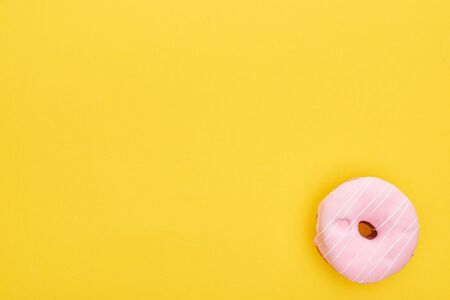 Top view of tasty pink glazed doughnut on bright yellow background Stock Photo