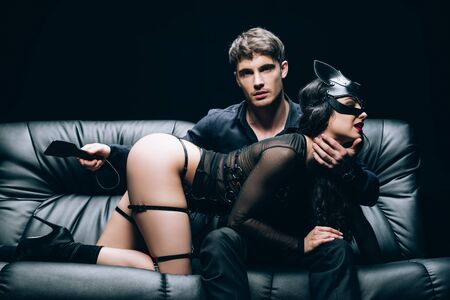 Passionate man sitting with leather spanking paddle near sexy woman in bdsm costume on leather sofa isolated on black background