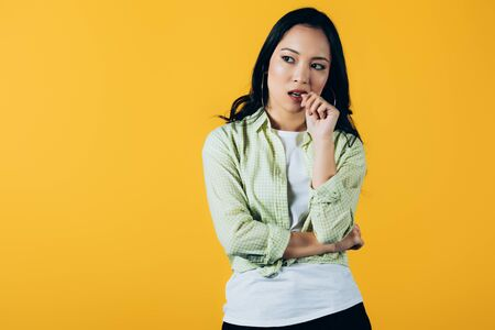 Attractive brunette Asian girl thinking isolated on yellow background Stock Photo