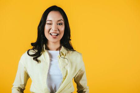 Attractive brunette Asian girl winking isolated on yellow background Stock Photo