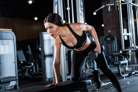 Low angle view of strong and athletic woman working out with dumbbell in gym