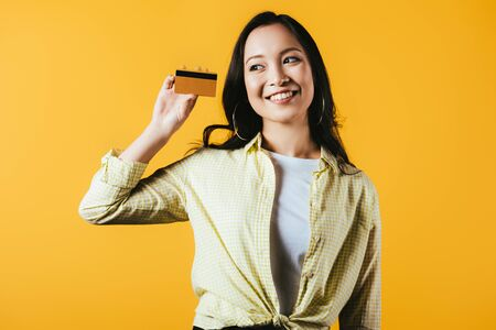 Chica asiática alegre con tarjeta de crédito, aislado sobre fondo amarillo