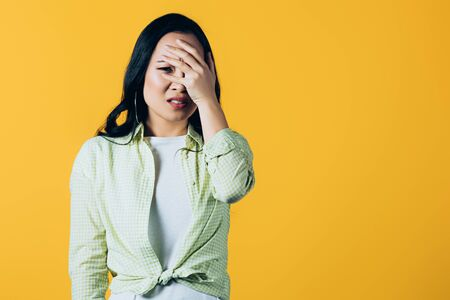 Scared brunette Asian girl closing face isolated on yellow background 스톡 콘텐츠