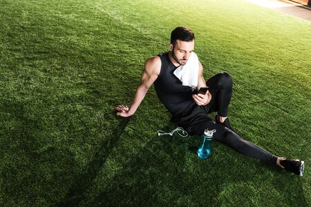 Handsome athletic man using smartphone while sitting on grass Фото со стока