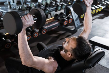 Overhead view of handsome strong man working out with dumbbells in gym