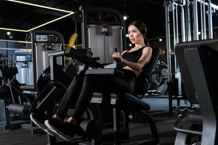 Low angle view of athletic woman exercising on training apparatus in gym