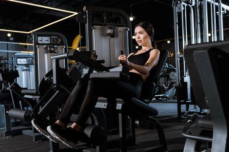 Niedrige Winkelsicht der athletischen Frau, die auf Trainingsgeräten im Fitnessstudio trainiert Standard-Bild