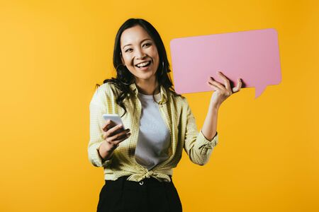 Happy Asian girl using smartphone and holding pink speech bubble, isolated on yellow background