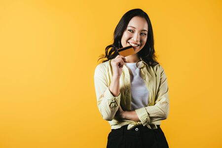 Cheerful Asian woman holding credit card, isolated on yellow background Stockfoto