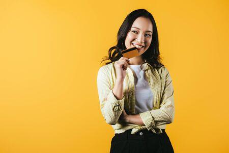 Fröhliche Asiatin mit Kreditkarte, isoliert auf gelbem Hintergrund