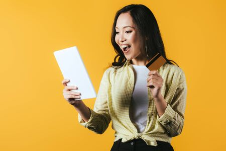 Excited Asian girl shopping online with digital tablet and credit card, isolated on yellow background Banco de Imagens