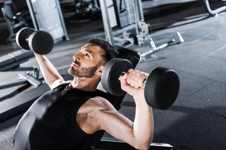 Selective focus of handsome strong man working out with dumbbells in gym