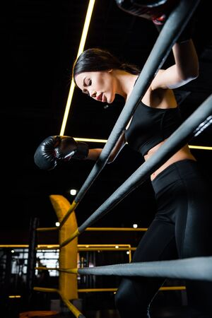 Low angle view of athletic woman in boxing gloves standing in gym