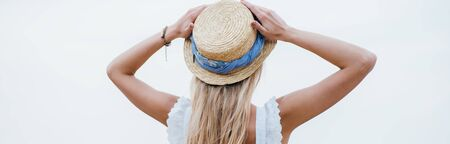 Panoramic shot of young blonde woman standing and touching straw hat Foto de archivo - 126606693