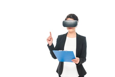 Young mixed race businesswoman in virtual reality headset holding clipboard isolated on white background Imagens