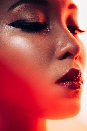 Attractive Asian woman in red light, toned picture