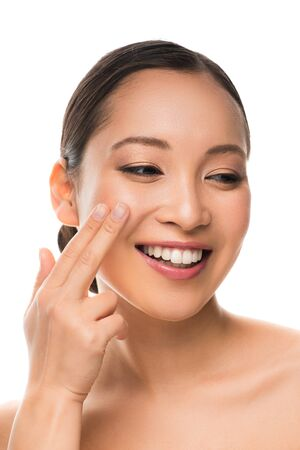 Attractive smiling Asian girl applying cream, isolated on white background Stock Photo