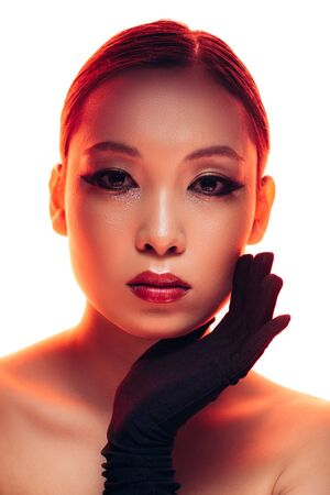 Beautiful Asian girl in black gloves with makeup in red light, isolated on white background