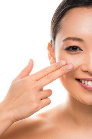 Beautiful smiling Asian girl applying cream, isolated on white background