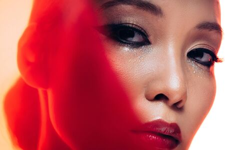 Perfect Asian woman with makeup in red light